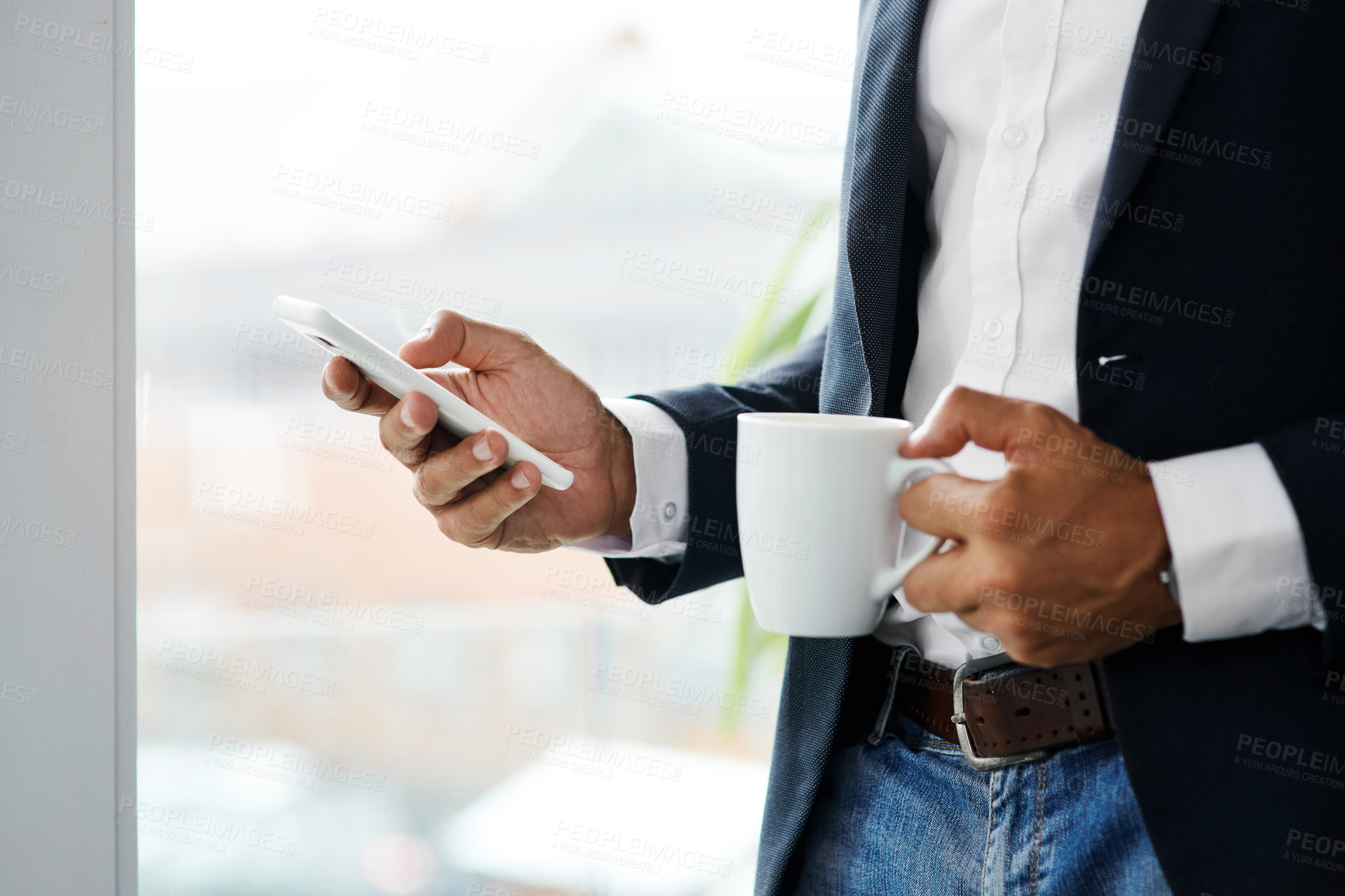 Buy stock photo Cropped shot of an unrecognisable businessman using a smartphone and having coffee in a modern office