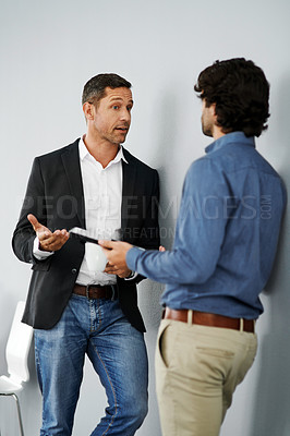 Buy stock photo Studio shot of two businessmen having a discussion against a grey background