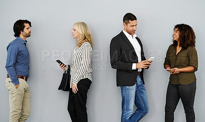 Buy stock photo Studio shot of a group of businesspeople chatting while waiting together against a grey background
