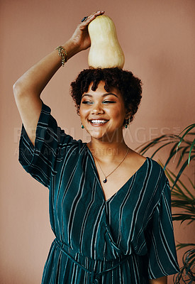 Buy stock photo Shot of a young woman holding a butternut on top of her head at home