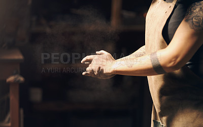 Buy stock photo Cropped shot of an unrecognisable woman dusting the dirt off of her hands while working at a foundry
