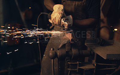 Buy stock photo Shot of a man using an angle grinder while working at a foundry
