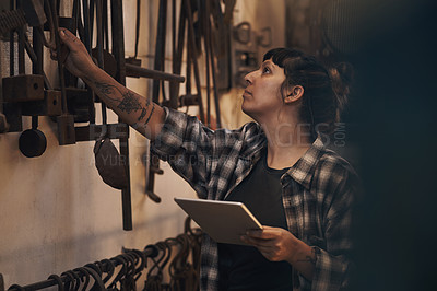 Buy stock photo Shot of a young woman using a digital tablet while working at a foundry