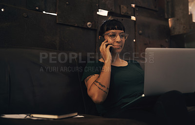 Buy stock photo Shot of a young woman using a laptop and smartphone while working at a foundry