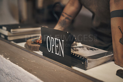 Buy stock photo Shot of a woman standing at the front desk with an open sign of a foundry