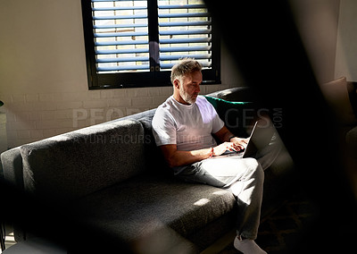 Buy stock photo Shot of a man using his laptop while sitting on the couch at home