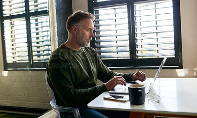 Buy stock photo Shot of a mature man using his laptop while sitting at home