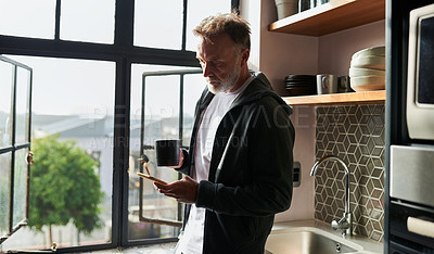 Buy stock photo Shot of a man drinking coffee while using his cellphone at home