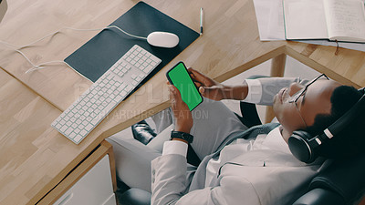 Buy stock photo Shot of a businessman wearing headphones while using his cellphone at his desk