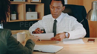 Buy stock photo Shot of two businesspeople doing paperwork while sitting together in an office