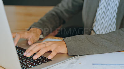 Buy stock photo Cropped shot of an unrecognizable woman working on a laptop in an office
