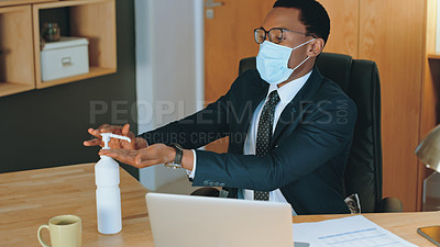 Buy stock photo Cropped shot of a businessman sanitising his hands and wearing a mask at his desk