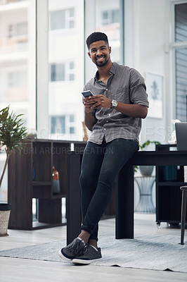 Buy stock photo Portrait of a young businessman using a cellphone in an office