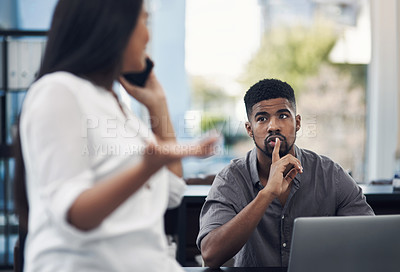 Buy stock photo Shot of a young businessman gesturing for his colleague to be quiet in an office