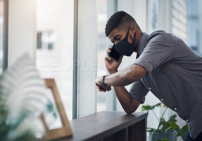 Buy stock photo Shot of a young businessman wearing a face mask and checking the time while talking on a cellphone in an office