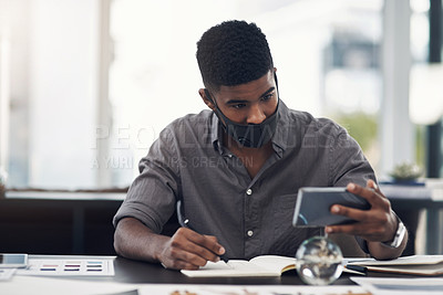 Buy stock photo Shot of a young designer writing notes while using a cellphone in an office