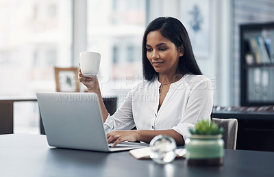 Buy stock photo Shot of a young businesswoman drinking coffee while working on a laptop in an office