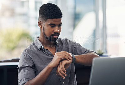 Buy stock photo Shot of a young businessman checking the time while working on a laptop in an office