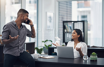 Buy stock photo Shot of a young businessman talking on a cellphone while his colleague is shrugging at her in an office