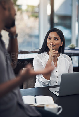 Buy stock photo Shot of a young businesswoman gesturing for her colleague to be quiet in an office