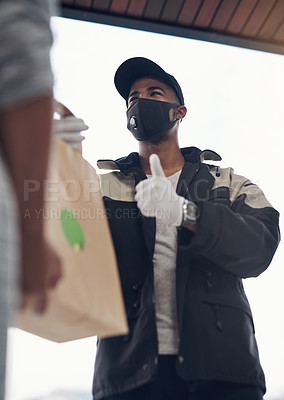 Buy stock photo Shot of a masked young man showing thumbs up while delivery takeout to a customer at home