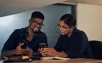 Buy stock photo Shot of two young technicians using their smartphone while repairing computer hardware