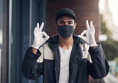 Buy stock photo Shot of a masked and gloved young man showing an okay sign while making a home delivery