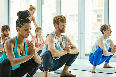 Buy stock photo Shot of a group of men and women practicing the garland pose during a yoga class
