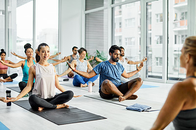 Buy stock photo Shot of a group of men and women meditating during a yoga class