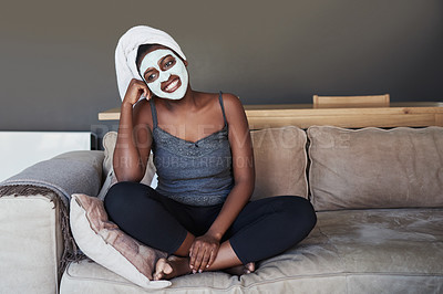 Buy stock photo Shot of a young woman wearing a face mask while sitting on the couch at home