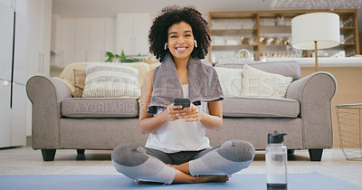 Buy stock photo Portrait of a young woman using a cellphone while exercising at home