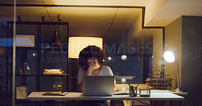Buy stock photo Shot of a young businesswoman looking stressed while using a laptop during a late night at work