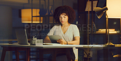 Buy stock photo Shot of a young businesswoman using a digital tablet and laptop during a late night in a modern office