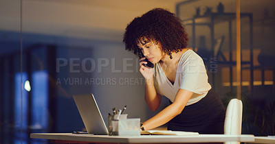 Buy stock photo Shot of a young businesswoman using a smartphone and laptop during a late night in a modern office