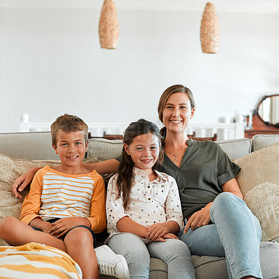 Buy stock photo Shot of a young boy and girl sitting at home with their mother