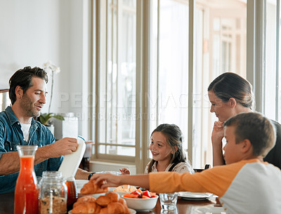 Buy stock photo Shot of a family of four having breakfast together at home