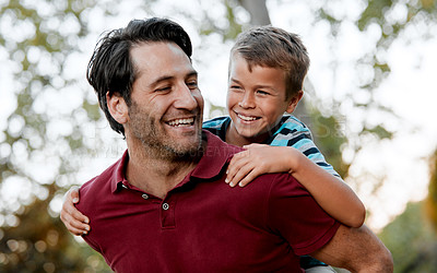 Buy stock photo Shot of a man giving his son a piggy-back ride while out at the park