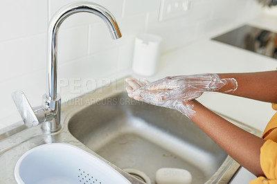 Buy stock photo Cropped shot of an unrecognizable woman washing her hands in the kitchen sink