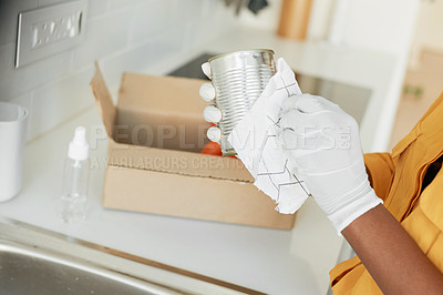Buy stock photo Cropped shot of an unrecognizable woman wiping her groceries before packing it away