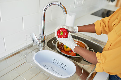 Buy stock photo Cropped shot of an unrecognizable woman rinsing vegetables in the kitchen sink