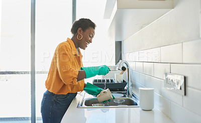 Buy stock photo Cropped shot of a young woman doing the dishes at home