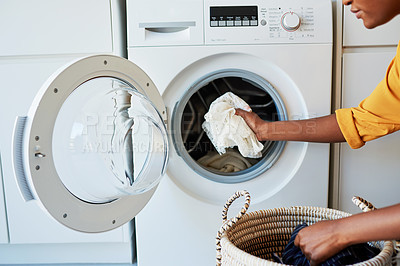 Buy stock photo Cropped shot of an unrecognizable woman doing her laundry at home