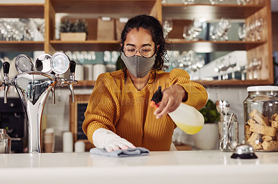 Buy stock photo Shot of a woman wearing a mask while cleaning the counter in a cafe