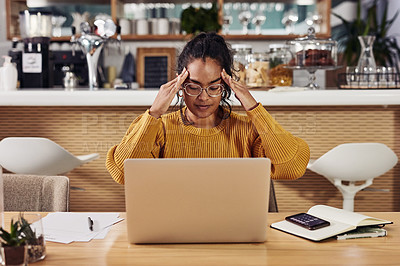 Buy stock photo Shot of a cafe owner looking stressed while working on her laptop