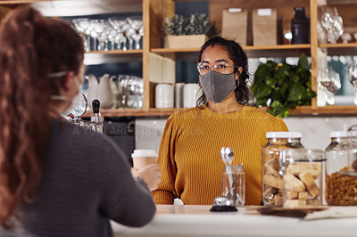 Buy stock photo Shot of a woman wearing a mask while serving a customer in a cafe