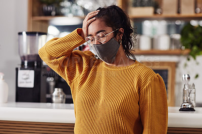Buy stock photo Shot of a woman wearing a mask and looking stressed in a cafe