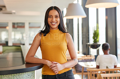 Buy stock photo Portrait of a confident young businesswoman standing at the front desk of a modern office