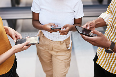 Buy stock photo Cropped shot of a group of businesspeople using their phones outdoors