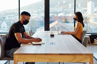 Buy stock photo Shot of a masked young businesswoman and businessman working apart from each other at a table in a modern office