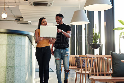 Buy stock photo Shot of a young businessman and businesswoman using a laptop while walking through a modern office